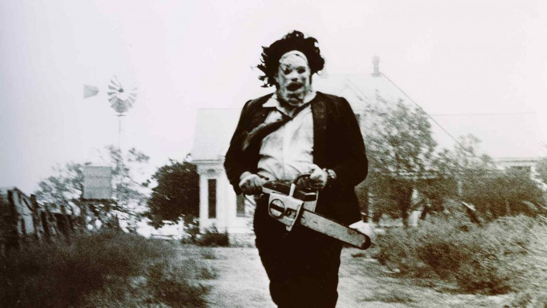 Leatherface from the movie The Texas Chainsaw Massacre chasing his victims to cut up with his chainsaw.