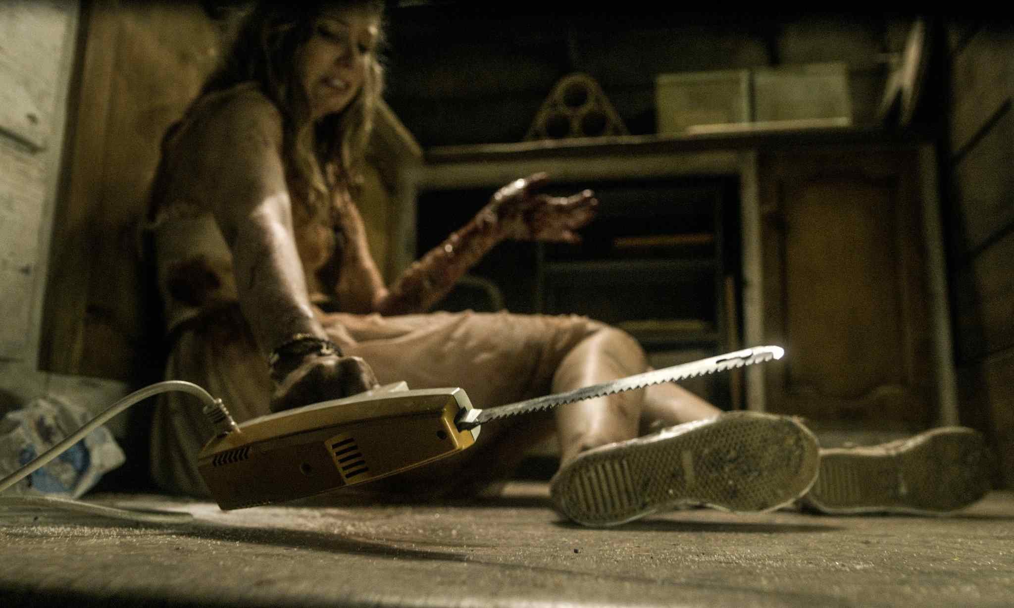 Natalie (Elizabeth Blackmore) in Fede Alvarez's Evil Dead 2013, about to cut her arm off with an electric carving knife.