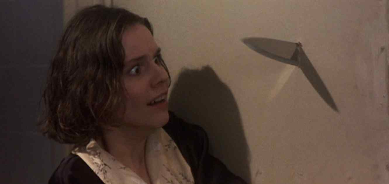 Billy Hughes (Marina Zudina) with a knife coming at her in the Anthony Waller helmed Horror-Thriller Mute Witness.