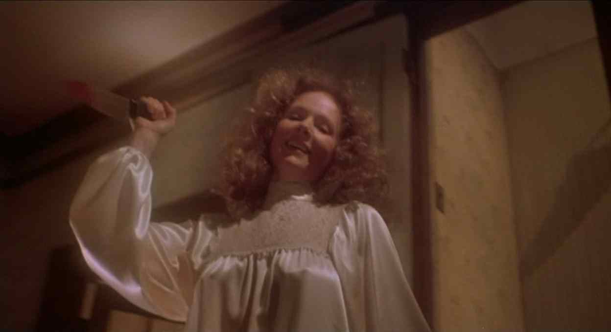 Piper Laurie as Margaret White in Carrie holds a knife over her head as she attacks her daughter.