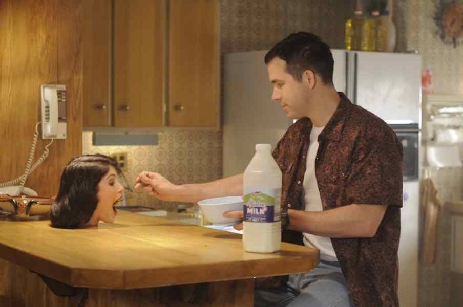 The Voices -- Ryan Reynolds feeds his severed head as Jerry in The Voices.