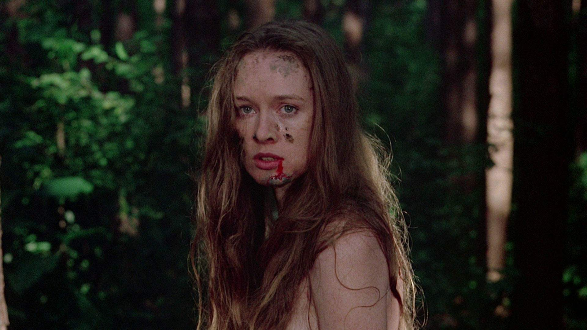 A dirty and bloody Jennifer wanders the woods after being assaulted in I Spit on Your Grave.