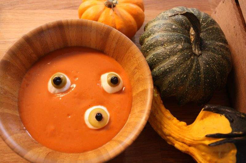 Spooky eyeball soup made out of tomato soup, mozzarella balls and olives topped with peppercorns.