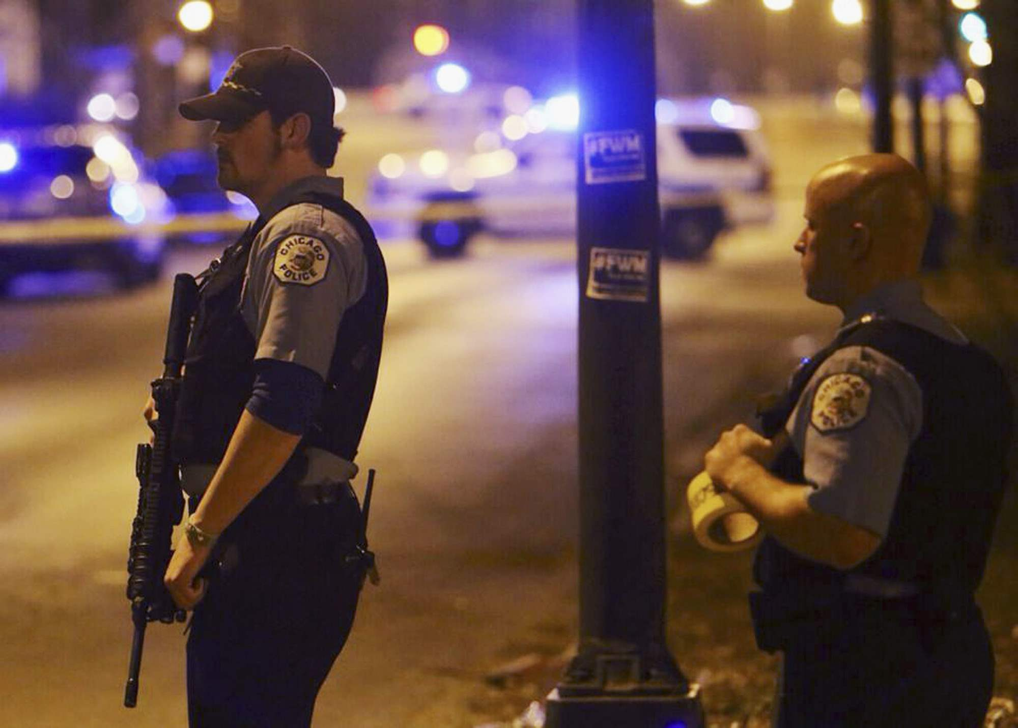 In this Sunday, April 20, 2014 photo, Chicago police stand guard at the scene where five children, all 15 years old or younger, were shot and wounded in Chicago. Police said Monday that eight people were killed and 44 injured, including the five children, in weekend shootings. (AP Photo/Sun-Times Media, Brian Jackson) MANDATORY CREDIT, MAGS OUT, NO SALES ** Usable by LA and DC Only **