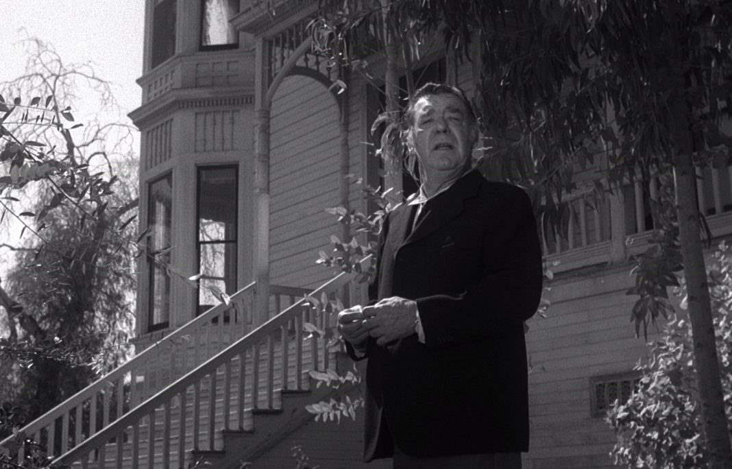 Lon Chaney Jr as Bruno in Spider Baby stands in front of the Merrye house