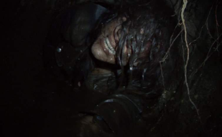 Lisa crawling through a dirt tunnel in Blair Witch