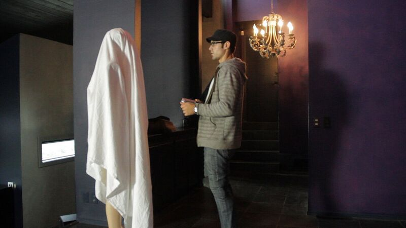 Andre inspects a mannequin covered in a sheet in It Watches