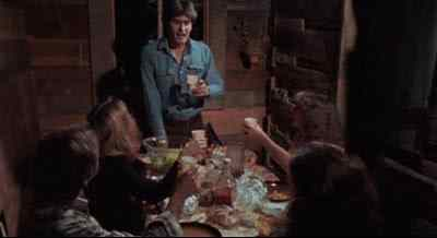 Ash at the head of the dinner table in a scene from Sam Raimi's 1981 horror film The Evil Dead - five great horror pictures that are based on a short