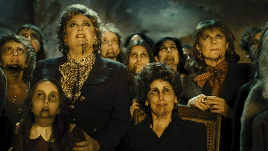 the witches from Witching and Bitching gather in the cave
